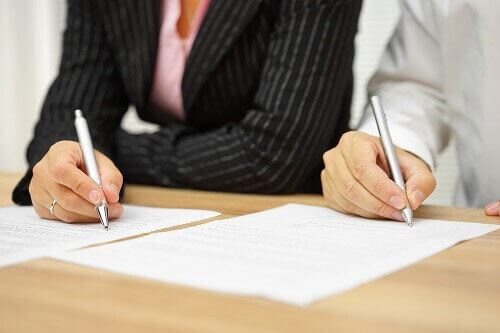 Couple signing prenuptial agreement